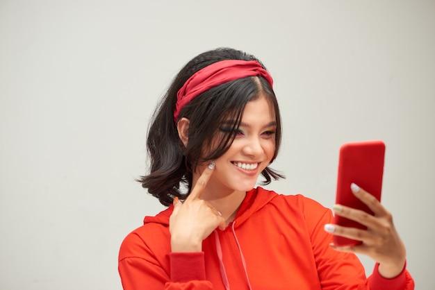 白い背景の上に携帯電話を保持している遊び心のある若い女性の肖像画