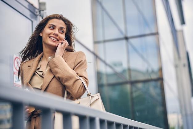 거리를 응시하는 그녀의 손에 핸드폰으로 기쁘게 여성 기업가의 초상화