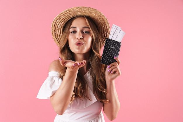 キスを吹くチケットとパスポートを保持しているピンクの壁の上に孤立してポーズをとって喜んで若いきれいな女性の肖像画。