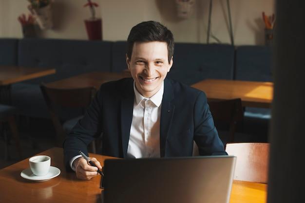 커피 숍에 앉아 웃고있는 동안 자신의 노트북에서 일하는 긍정적 인 자신감 백인 기업가의 초상화.