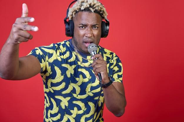 Портрет позитивного, наслаждающегося красивым африканским мужчиной с микрофоном и наушниками на голове
