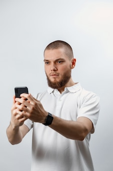 Портрет положительного красивого бородатого мужчины в белой футболке разговаривает по видеовызову с помощью смартфона