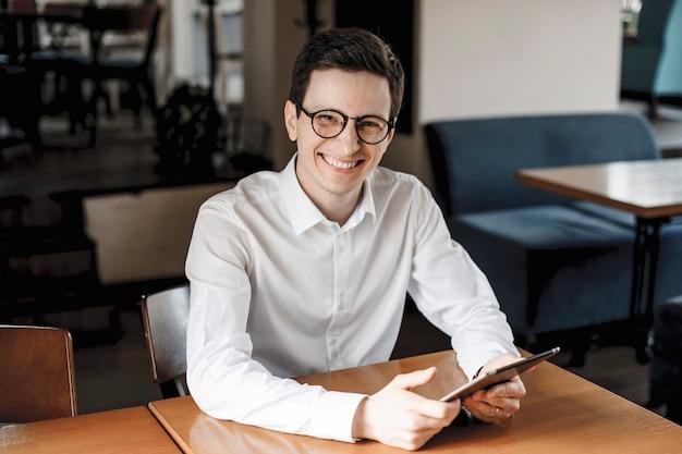 机に座って、眼鏡をかけてタブレットを持って笑顔のカメラを見ている前向きなハンサムな若い男性の肖像画。