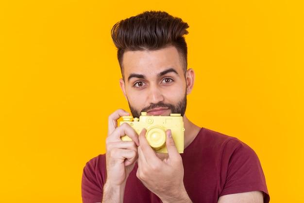 그의 손에 노란색 빈티지 카메라를 들고 수염을 가진 긍정적 인 잘 생긴 젊은 남자의 초상화. 사진의 개념. 광고 공간