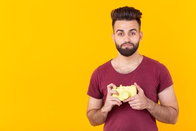 手に黄色のビンテージカメラを持っているひげを持つポジティブなハンサムな若い男の肖像画
