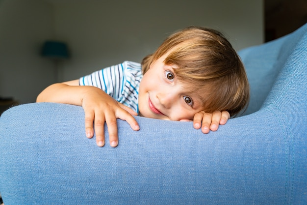 집에서 아늑한 안락의자에 앉아 웃고 있는 긍정적인 장난기 어린 소년의 초상화.