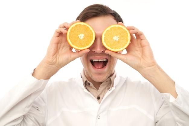 Портрет положительного улыбающегося мужского врача-диетолога с апельсинами. ешьте витамин с, оставайтесь здоровыми, диетическое питание в сезон простуды и гриппа