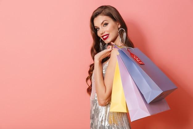 Портрет позитивной улыбающейся женщины в ярком платье с блестками, изолированной над розовой стеной, держащей хозяйственные сумки.