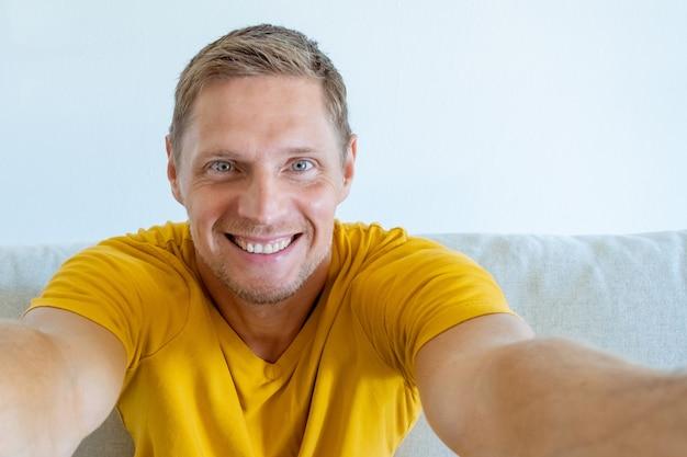 黄色のtシャツを着たポジティブな若い男の肖像画。自撮りをしている幸せな男。