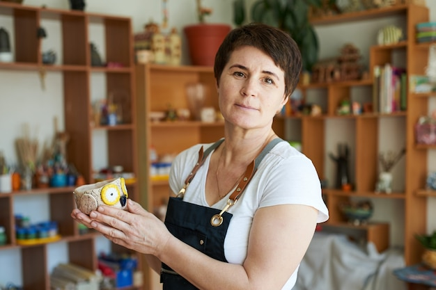 완성 된 작품을 보여주는 도자기 마스터 여자의 초상화.