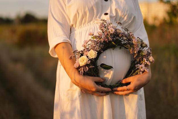 Портрет беременной женщины красивая молодая беременная женщина в белом платье гуляет в поле