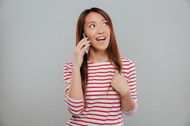 携帯電話で話しているかなりアジアの少女の肖像画