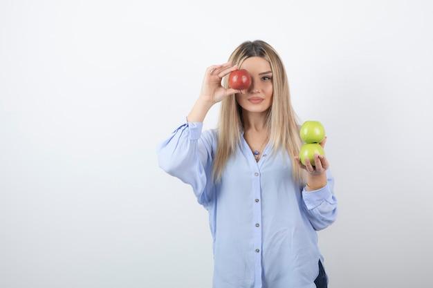 빨간 신선한 사과로 눈을 덮고 서 있는 꽤 매력적인 여성 모델의 초상화.