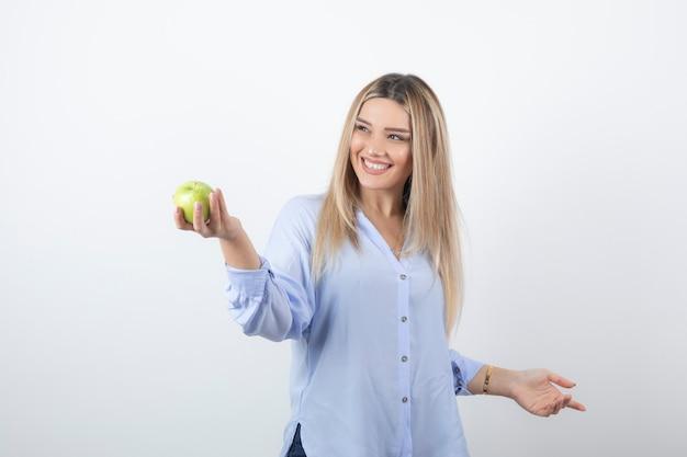 녹색 신선한 사과를 들고 서서 꽤 매력적인 여성 모델의 초상화.