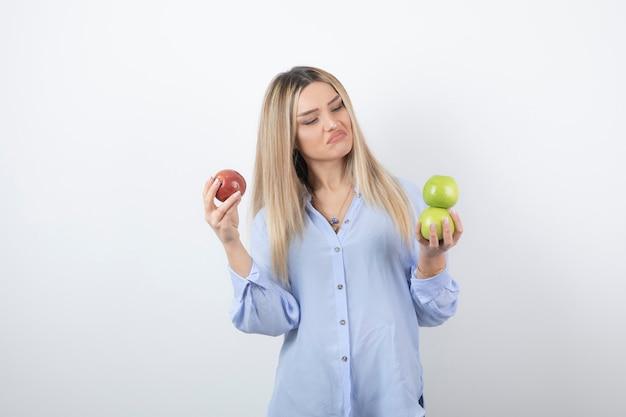 新鮮なリンゴを立って保持しているかなり魅力的な女性モデルの肖像画。