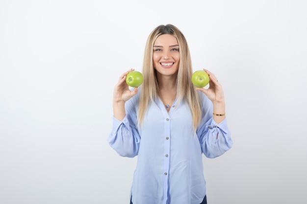 신선한 사과를 들고 서 있는 꽤 매력적인 여성 모델의 초상화.