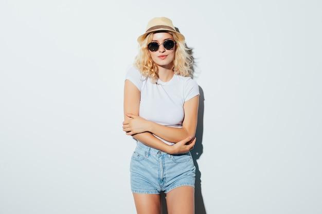 Портрет довольно красивой блондинки в пляжной шляпе на белой стене