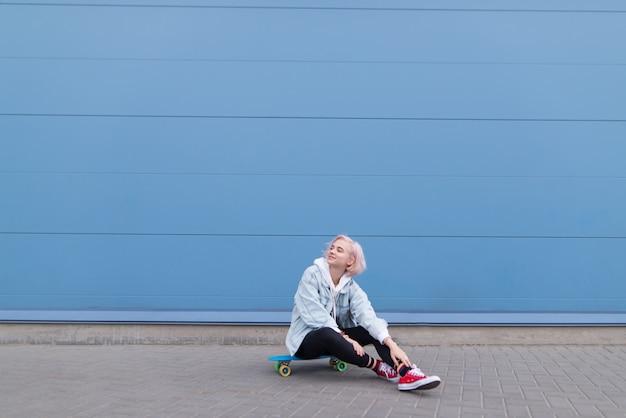 水色の壁でスケートボードの上に座って赤いスニーカーでかなりブロンドの女の子の肖像画