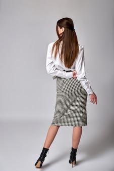 Портрет довольно брюнетка женщина, одетая в белую рубашку и клетчатую юбку. серая стена.