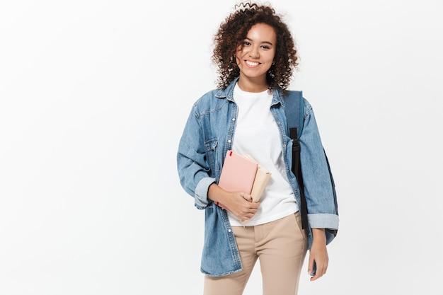 白い壁の上に孤立して立って、教科書を保持しているバックパックを運ぶかなり陽気なカジュアルなアフリカの女の子の肖像画
