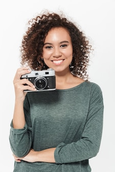 白い壁の上に孤立して立っている、写真カメラを保持しているかなり陽気なカジュアルなアフリカの女の子の肖像画