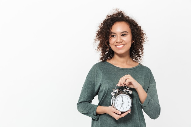 目覚まし時計を示して、白い壁の上に孤立して立っているかなり陽気なカジュアルなアフリカの女の子の肖像画