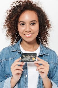 プラスチック製のクレジットカードを示す、白い壁の上に孤立して立っているかなり陽気なカジュアルなアフリカの女の子の肖像画