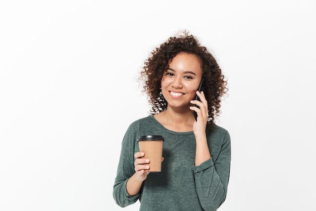 Портрет довольно веселой случайной африканской девушки, стоящей изолированно над белой стеной, разговаривающей по мобильному телефону и пьющей кофе на вынос