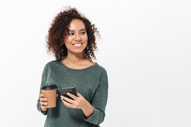 Портрет довольно веселой случайной африканской девушки, стоящей изолированно над белой стеной, с помощью мобильного телефона и пьющей кофе на вынос