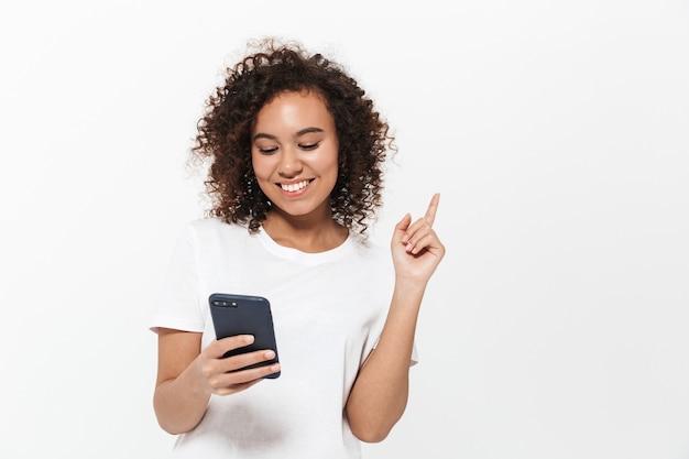 白い壁の上に孤立して立っている、携帯電話を使用して、指を離れて指しているかなり陽気なカジュアルなアフリカの女の子の肖像画