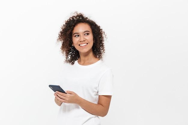 携帯電話を使用して、白い壁の上に孤立して立っているかなり陽気なカジュアルなアフリカの女の子の肖像画