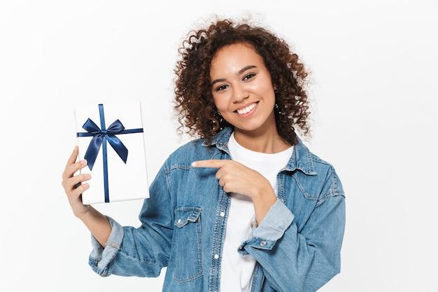 Портрет довольно веселой возбужденной случайной африканской девушки, стоящей изолированно над белой стеной, показывая подарочную коробку, празднуя