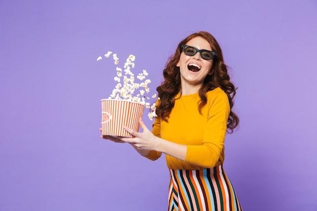Портрет довольно веселой молодой рыжеволосой женщины, стоящей над фиалкой и поедающей попкорн