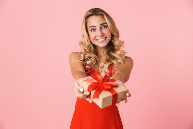 Портрет довольно возбужденной счастливой молодой милой белокурой женщины, позирующей изолированной над розовой стеной, держащей настоящую подарочную коробку.