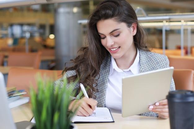 図書館でノートパソコンを持っているきれいな女子学生の肖像画。