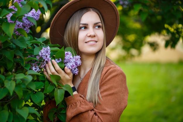 庭にライラックと茶色の帽子をかぶったかわいい女の子の肖像画