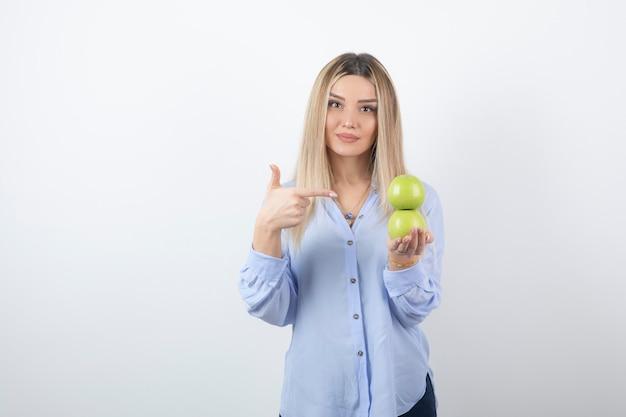 新鮮なリンゴを指しているかわいい女の子モデルの肖像画。
