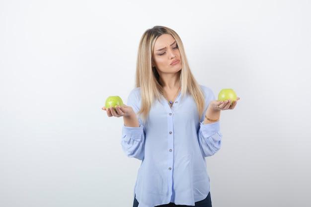 Портрет красивой девушки модели стоя и держа свежие яблоки.