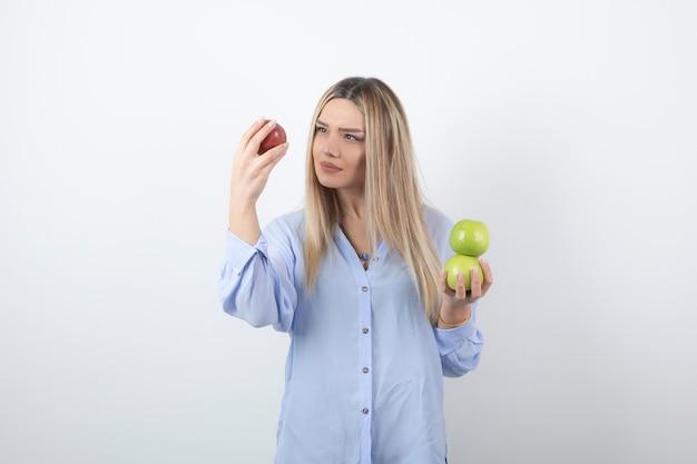 新鮮なリンゴを立って保持しているかわいい女の子モデルの肖像画。