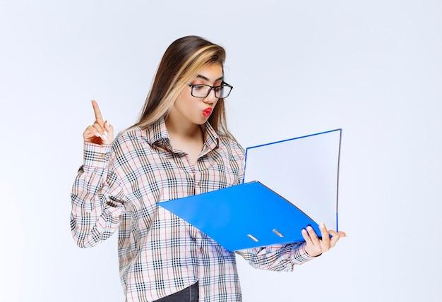 立って、白い背景の上の青いフォルダーを見ているかわいい女の子の肖像画。