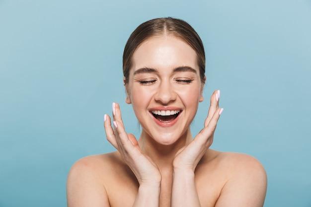 Портрет довольно счастливой жизнерадостной молодой женщины, позирующей изолированной над голубой стеной.