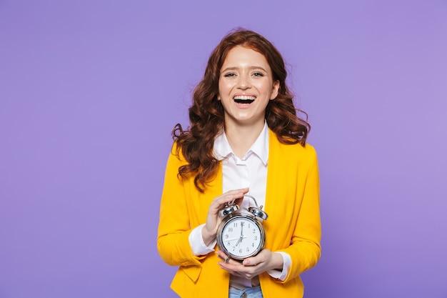 目覚まし時計を表示して、紫の上に立っているかなり幸せな若い赤毛の女性の肖像画