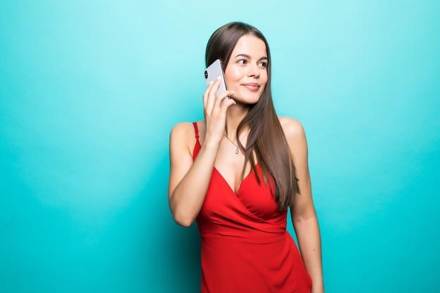 Портрет довольно радостной девушки в платье разговаривает по мобильному телефону, изолированной над синей стеной
