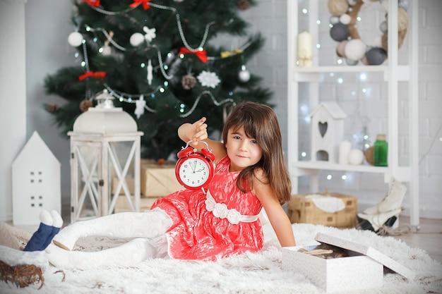 Портрет красивой маленькой брюнетки, держащей в руках красный будильник в интерьере с елочными украшениями