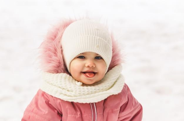 Портрет красивой маленькой девочки в белой шляпе зимой на природе