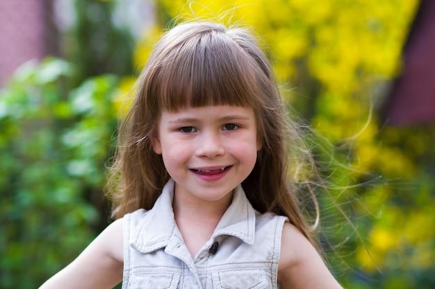 ぼやけた屋外に対してカメラに恥ずかしそうに笑ってノースリーブの白いドレスのかわいい長い髪のブロンド幼児少女の肖像画。罪のない幸せな子供時代のコンセプトです。