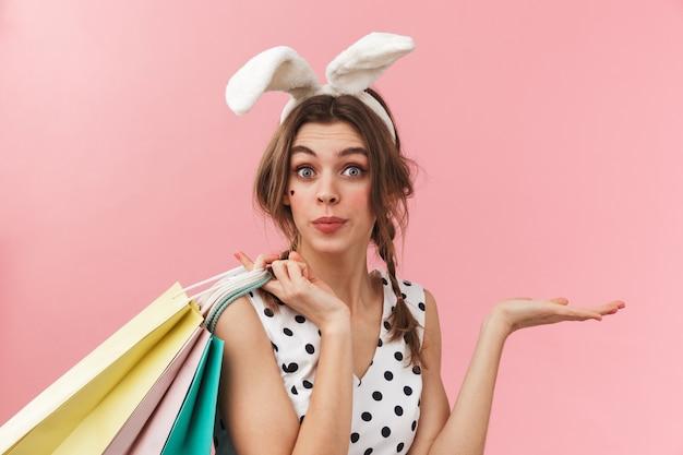 Портрет довольно милой девушки с кроличьими ушками стоит изолированно, неся сумки для покупок
