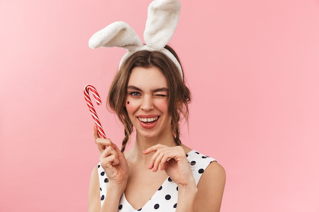 Портрет довольно милой девушки с кроличьими ушками, стоящей изолированно, гримасничая и держащей конфету