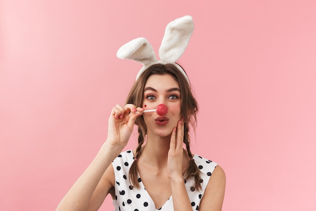Портрет довольно милой девушки с кроличьими ушками стоит изолированно, гримасничая, держа леденец на палочке