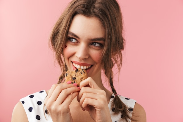Портрет довольно милой девушки в платье стоит изолированно и ест шоколадное печенье